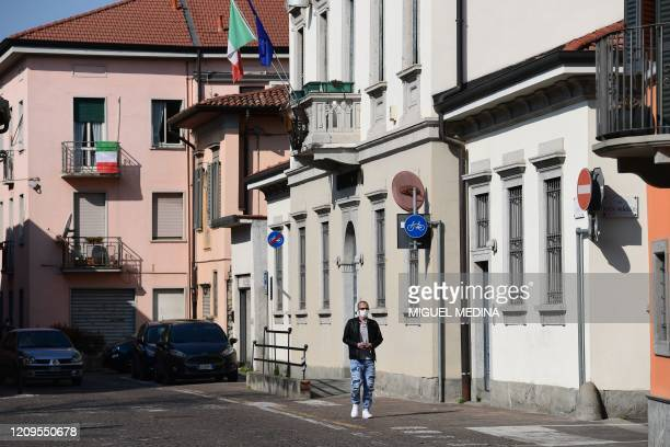 Man wearing a face mask walks past the city hall on April 9, 2020 in Treviolo, near Bergamo, Lombardy, during the country's lockdown aimed at...