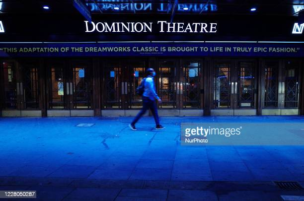 Man wearing a face mask walks past the Dominion Theatre, home to musical 'The Prince of Egypt', at St Giles Circus in London, England, on August 14,...