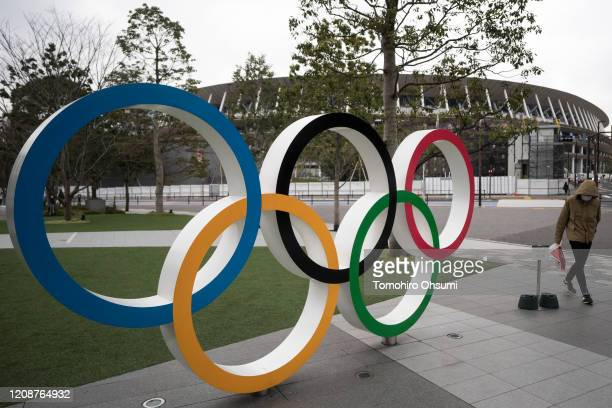 A man wearing a face mask walks past the Olympic rings in front of the new National Stadium the main stadium for the upcoming Tokyo 2020 Olympic and...