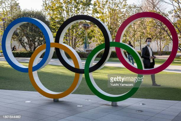 Man wearing a face mask walks past the Olympic Rings on February 11, 2021 in Tokyo, Japan. Yoshiro Mori, the head of the Tokyo Olympics and...