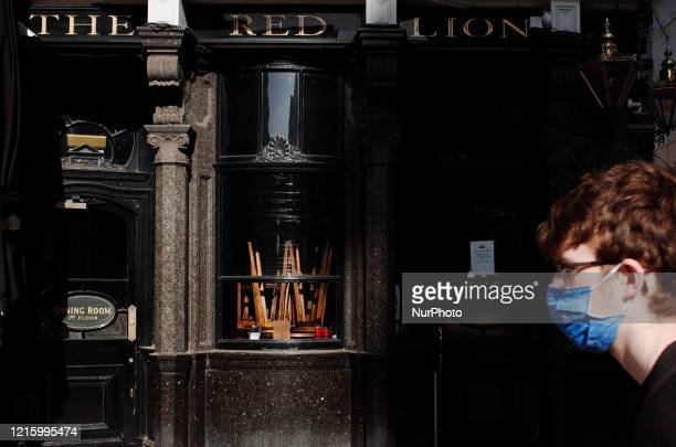 Man wearing a face mask walks past upturned stools in the window of The Red Lion pub, closed due to coronavirus, on a near-deserted Whitehall in...