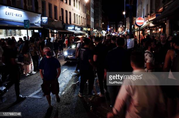 Man wearing a face mask walks through crowds of revellers on Old Compton Street in the hospitality and nightlife hotspot of Soho in London, England,...