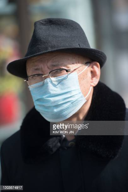A man wearing a face mask walks through Kwangbok street in Pyongyang on February 26 2020 The novel coronavirus has killed over 2700 people and...