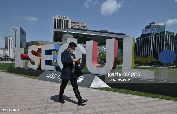 A man wearing a face mask walks through Seoul Plaza in front of the city hall in Seoul on April 23 2020 South Korea's economy saw its worst...