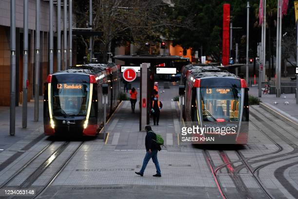 Man wearing a face mask walks towards tram station at Circular Quay in Sydney on July 19 amid a lockdown in Melbourne and Sydney as Australia seeks...