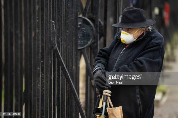 Man wearing a face mask watches as members of the Coldstream Guards prepare to march to Buckingham Palace on the day that Queen Elizabeth II is set...