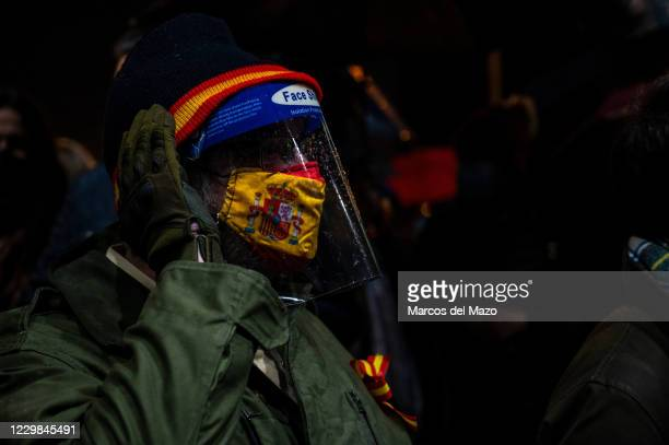 Man wearing a face shield and a face mask with a Spanish flag to protect against the spread of coronavirus protesting against censorship in Social...