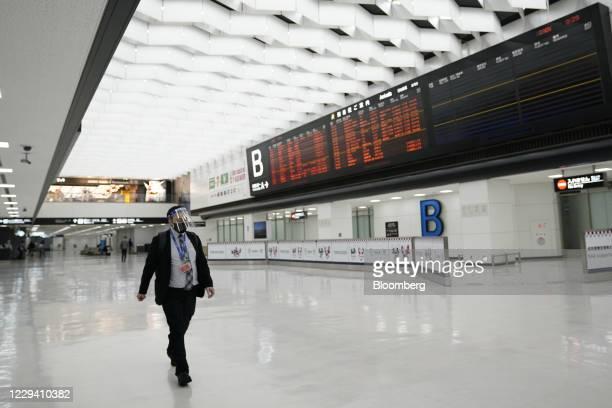 Man wearing a face shield walks past a flight arrival information board at Narita International Airport in Narita, Chiba Prefecture, Japan, on...