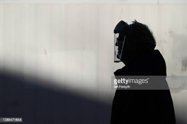 Man wearing a face shield walks through Hull city centre on November 13, 2020 in Hull, England. Hull recorded 726.8 new cases per 100,000 people in...