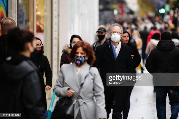 Man wearing a face wask walks amid shoppers on Oxford Street in London, England, on December 4, 2020. London has returned to so-called Tier 2 or...