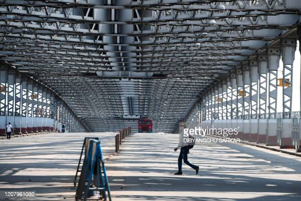 A man wearing a facemaks crosses the road on the Howrah Bridge during a oneday Janata curfew imposed amid concerns over the spread of the COVID19...