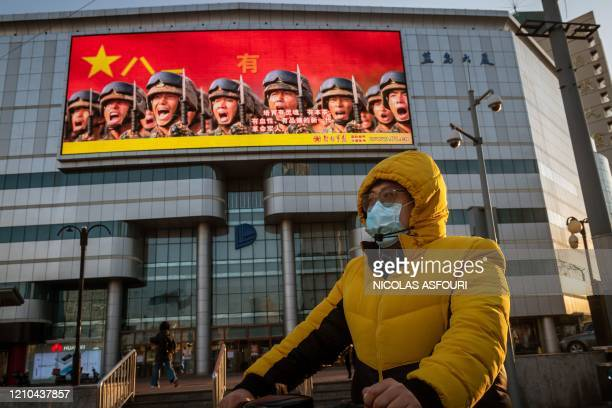 Man wearing a facemask amid the concerns over the COVID-19 coronavirus waits at a traffic red light on his bicycle in front of a screen displaying a...