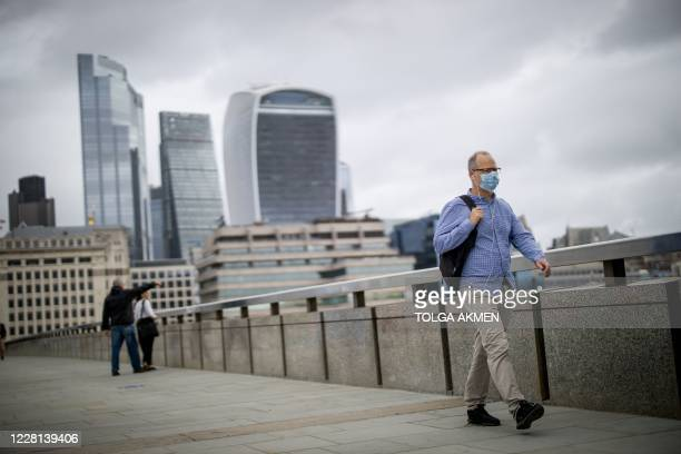 Man wearing a facemask as a precaution against the spread of the novel coronavirus walks across London Bridge with the offices of the City of London...