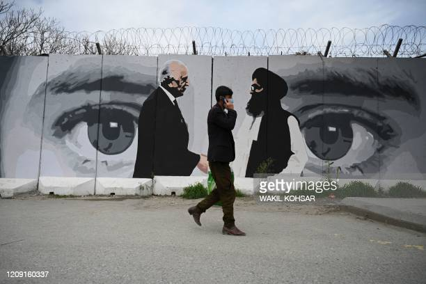 Man wearing a facemask as a precautionary measure against the COVID-19 novel coronavirus walk past a wall painted with images of US Special...