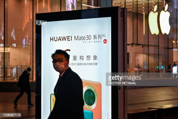 A man wearing a facemask as a preventive measure against the COVID19 novel coronavirus stands next to a Huawei advertisement near and Apple store in...