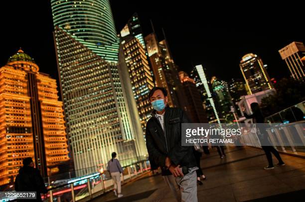 Man wearing a facemask as a preventive measure against the Covid-19 coronavirus walks over a bridge in the financial district of Lujiazu in Shanghai...