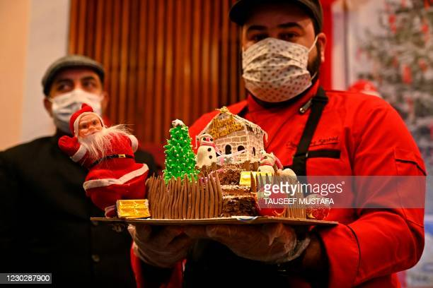 Man wearing a facemask as a preventive measure against the Covid-19 coronavirus holds a Christmas cake during a function organised by the Jammu and...