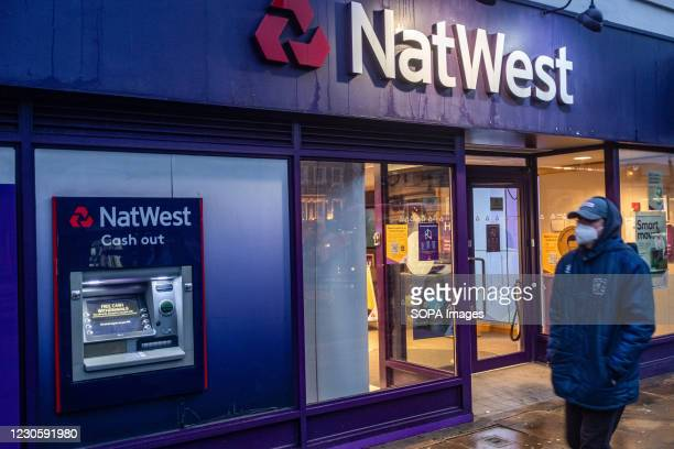 Man wearing a facemask as a preventive measure against the Covid-19 coronavirus walks past a branch of NatWest Bank in London.