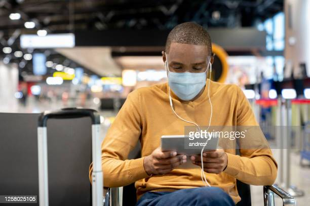 man wearing a facemask at the airport while watching movies on his tablet at the gate - station stock pictures, royalty-free photos & images