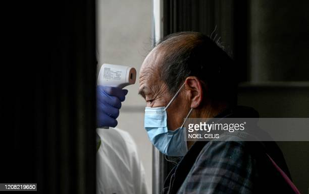 Man wearing a facemask has his temperature checked as he arrives at Macheng railway station, after a months-long lockdown as a preventive measure...