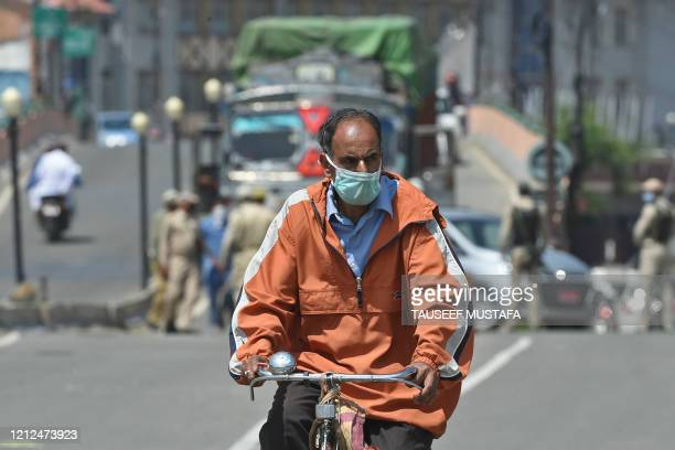 Man wearing a facemask rides a bicycle during a government-imposed nationwide lockdown as a preventive measure against the COVID-19 coronavirus, in...