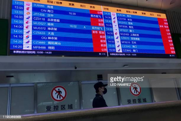 A man wearing a facemask stands under a screen showing mostly cancelled flights at Tianhe airport in Wuhan in China's central Hubei province on...