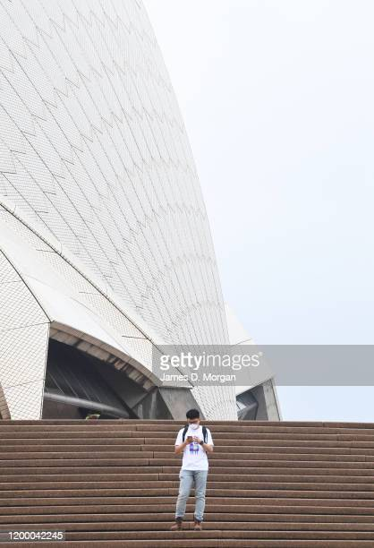 A man wearing a facemask uses his mobile phone in front of the Opera House between rain showers on January 17 2020 in Sydney Australia A severe...