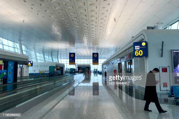 A man wearing a facemask walks at Tianhe airport in Wuhan in China's central Hubei province on January 23 2020 China banned trains and planes from...