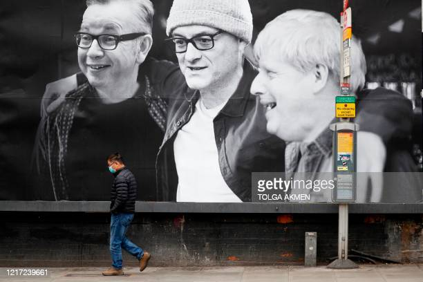 Man wearing a facemask walks past a billboard featuring Britain's Chancellor of the Duchy of Lancaster Michael Gove, Number 10 special advisor...