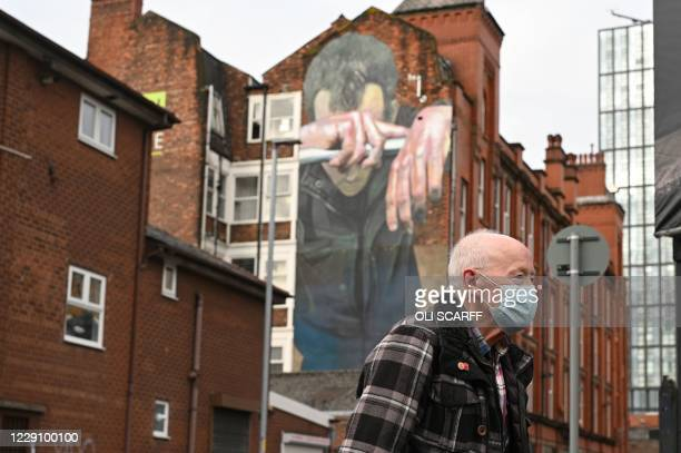 Man wearing a facemask walks past a mural painted as part of the Cities of Hope festival in 2016 and highlighting the effects of mental health, in...