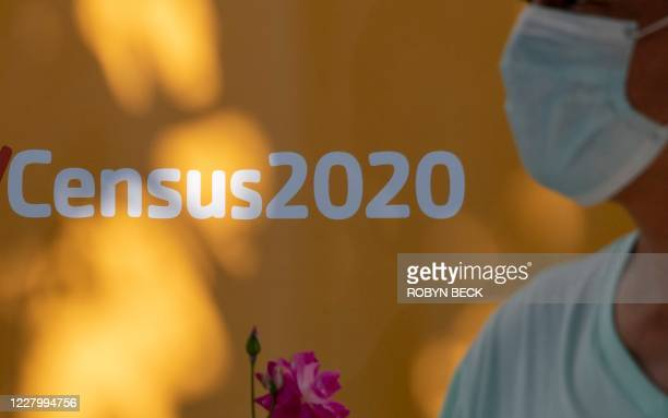 A man wearing a facemask walks past a sign encouraging people to complete the 2020 US Census in Los Angeles California August 10 2020 amid the...