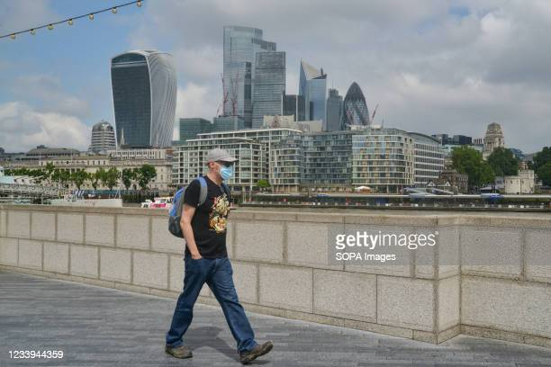 Man wearing a facemask walks past a view of London's skyline at London Bridge Thames path.