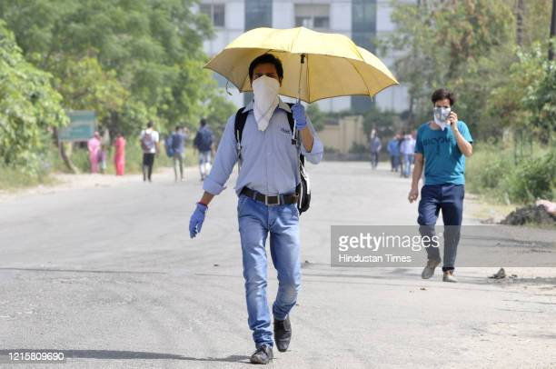 Man wearing a facemask walks with an umbrella on a hot summer day, on May 27, 2020 in Noida, India.