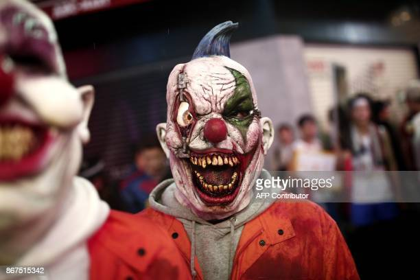 A man wearing a false bloodcovered clown mask walk in a street during a Halloween parade in Tokyo on late October 28 2017 / AFP PHOTO / Behrouz MEHRI