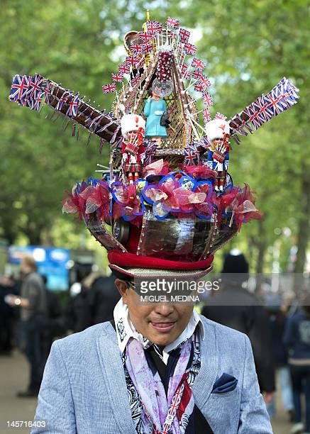 A man wearing a fancy hat poses on the Mall in London on June 4 in preparation for the Queen's Jubilee concert outside Buckingham Palace A chain of...