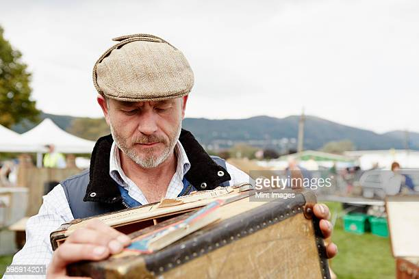 Man wearing a flat cap looking at a vintage suitcase at a flea market.