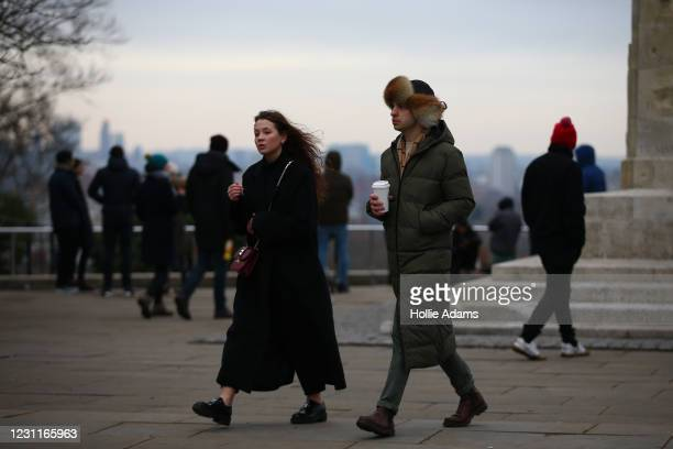 Man wearing a fur hat at Greenwich Park on February 14, 2021 in London, England. Frozen fountains and ponds around the capital started to thaw as...