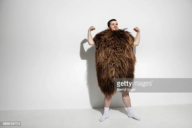 man wearing a fur suit and flexing - caveman stock photos and pictures