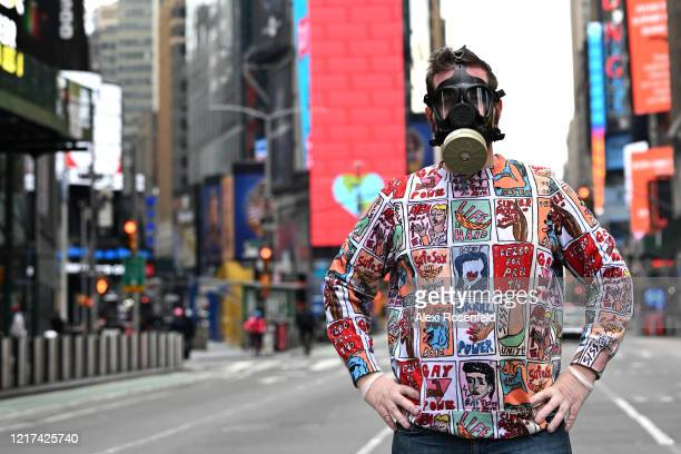 A man wearing a gas mask and gloves poses in Times Square amid the coronavirus pandemic on April 05 2020 in New York City COVID19 has spread to more...