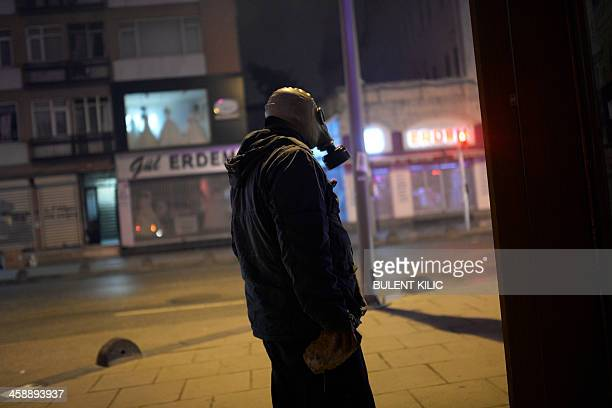 A man wearing a gas mask looks on while holding a stone as protestors clash with Turkish police during a demonstration on December 22 2013 in the...