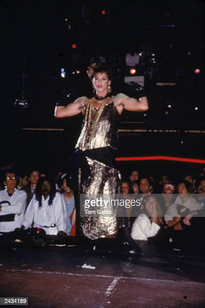 A man wearing a gold lame gown performs in front of a crowd during Halloween celebrations at Studio 54 New York City 1984