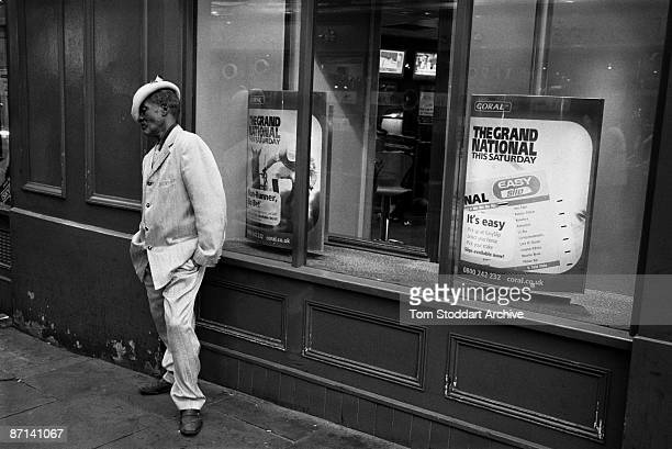 A man wearing a gold suit and hat stands outside a betting shop in the Soho district of London's West End March 2007