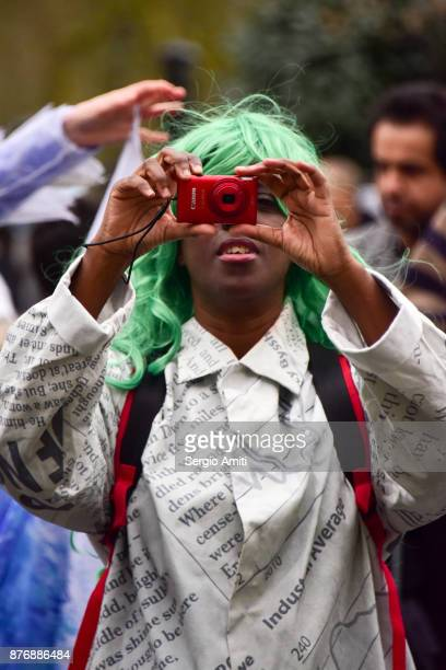 Man wearing a green wig takes a picture with a red compact camera