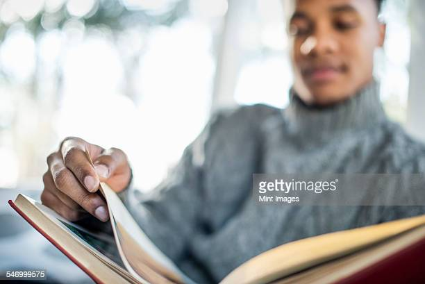 Man wearing a grey roll-neck jumper flipping through the pages of a book.