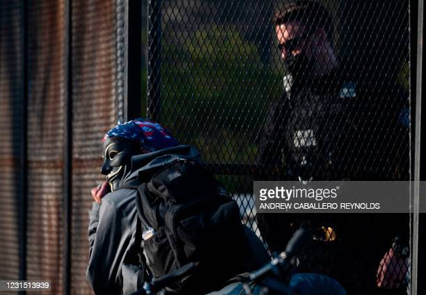 """Man wearing a """"Guy Fawkes"""" mask is confronted by members of the US Secret Service, near the White House in Washington, DC, on March 4, 2021. -..."""