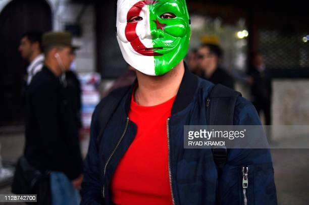 A man wearing a Guy Fawkes mask painted with the Algerian national flag poses for a photograph as students demonstrate in the capital Algiers on...