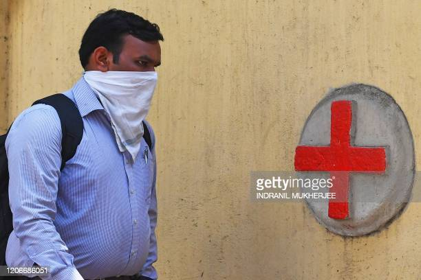 A man wearing a handkerchief amid concerns of the spread of the COVID19 coronavirus arrives at a hospital in Mumbai on March 12 2020