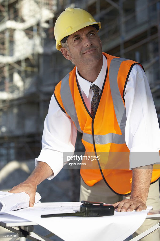 Man Wearing a Hard Hat and Fluorescent Jacket Looking Up From Building Plans : Stock Photo