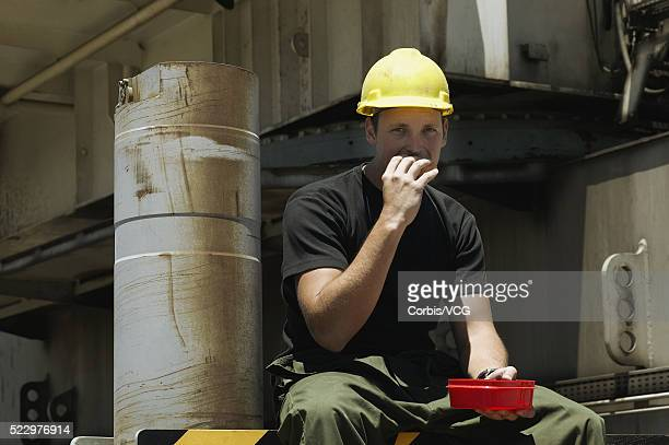 A man wearing a hard hat eating from a lunchbox