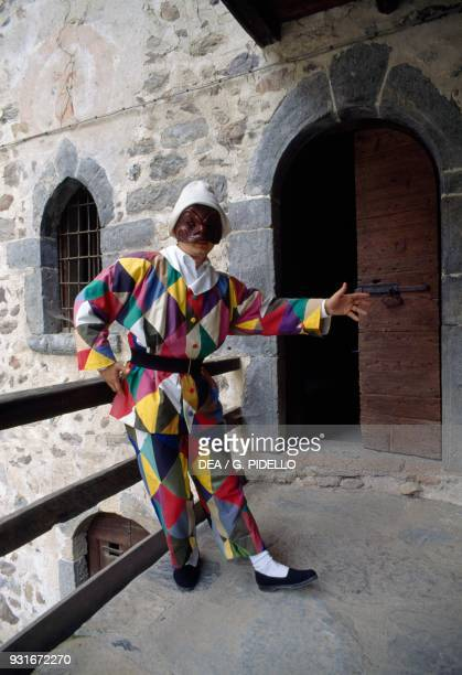 Man wearing a harlequin mask at the door to his house in Oneta Lombardy Italy